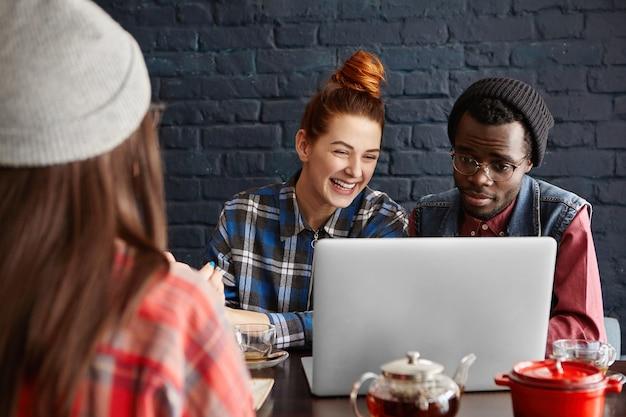 Modieuze afrikaanse student die hoed en bril draagt die open laptop met verbaasde blik zit
