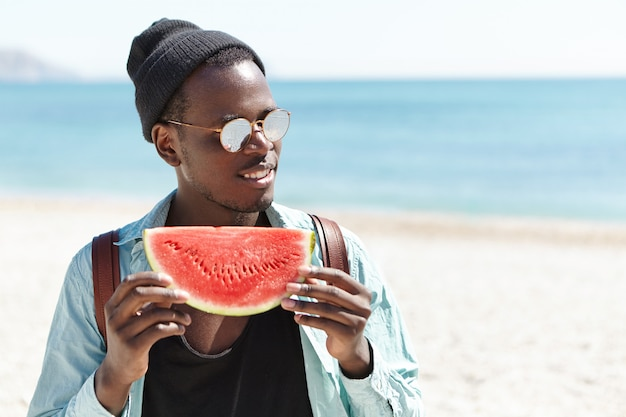 Modieuze afro-amerikaanse man in zwarte hoed en zonnebril die zich gelukkig en zorgeloos voelt met een groot stuk rijk rood-rijpe watermeloen terwijl hij de zomerdag buiten doorbrengt op het stedelijke strand