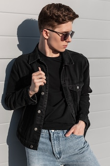 Modieuze amerikaanse jonge man in vintage zonnebril in stijlvolle casual denim kleding voor de jeugd