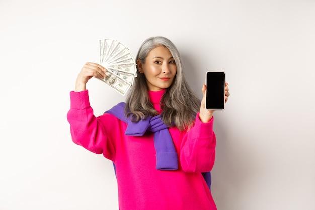 Modieuze aziatische senior vrouw die gelddollars en een leeg smartphonescherm toont, online winkel demonstreert, staande op een witte achtergrond