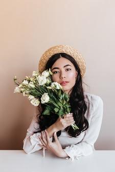 Modieuze aziatische vrouw die in strohoed witte eustomas houdt. vooraanzicht van mooie krullende vrouw met bloemboeket op beige achtergrond.