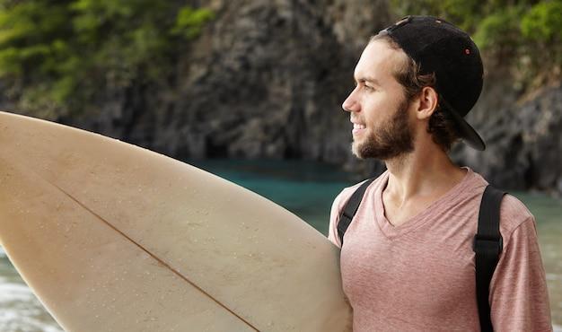 Modieuze bebaarde surfer in snapback met surfplank die op het strand staat en op zee kijkt, kijkend naar andere atleten die golven berijden tijdens de surfwedstrijd