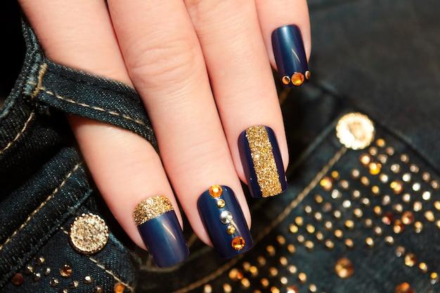 Modieuze blauwe manicure op vierkante nagels met gouden pailletten