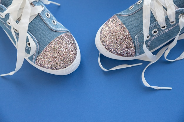 Modieuze blauwe sneakers voor meisjes geïsoleerd op blauwe muur. paar trendy sportschoenen voor kinderen.grande denim sneakers voor kinderen.paar trendy glanzende sneakers, met witte veters. jeugdstijl