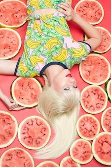 Modieuze blonde met make-up die dichtbij watermeloenen ligt Premium Foto