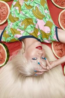 Modieuze blonde met make-up die dichtbij watermeloenen ligt