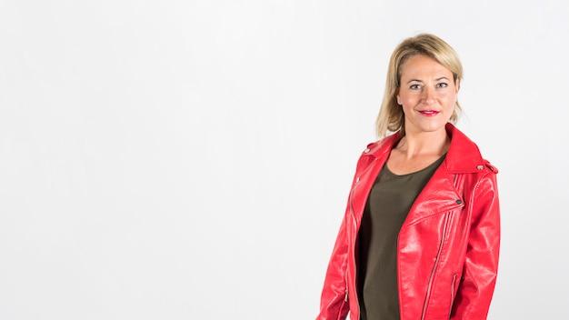 Modieuze blonde rijpe vrouw in rood leerjasje tegen witte achtergrond