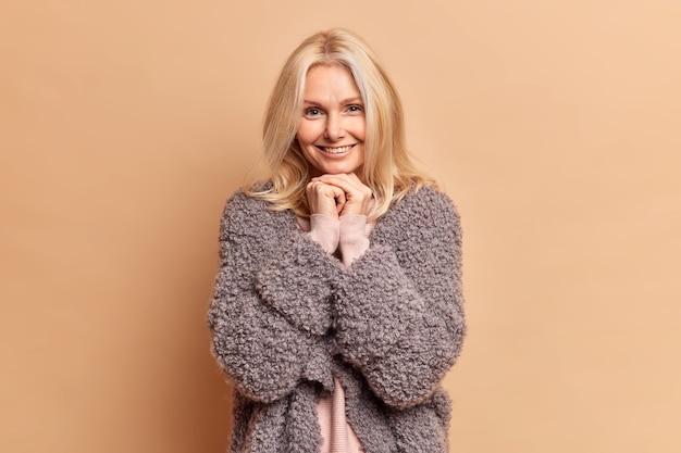 Modieuze blonde veertig jaar oude vrouw houdt handen onder de kin en glimlacht zachtjes draagt warme winterjas heeft minimale make-up poses tegen bruine studiomuur