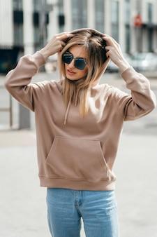 Modieuze blonde vrouw in bruine oversized hoodie