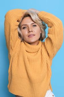 Modieuze blonde vrouw in een gebreide trui poseert voor de camera op een blauwe muur