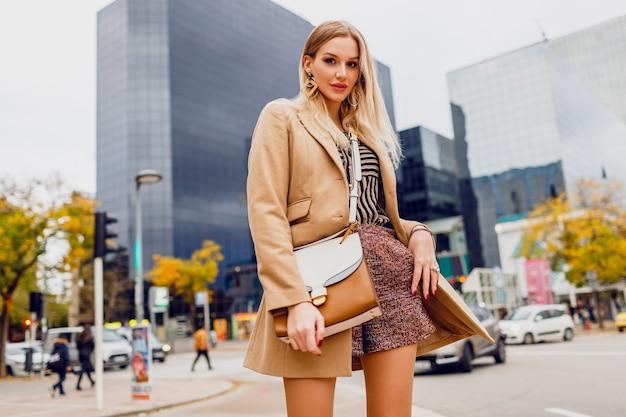 Modieuze blonde vrouw in lente casual outfit buiten wandelen en genieten van vakantie in grote moderne stad. droeg een wollen beige jas en een gestripte blouse. stijlvolle accessoires.