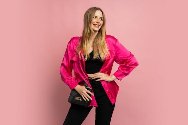 Modieuze blonde vrouw in stijlvolle zomerkleren die zich voordeed op roze muur