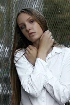 Modieuze blonde vrouw met lang haar draagt een wit overhemd poseren in de buurt van metalen hek