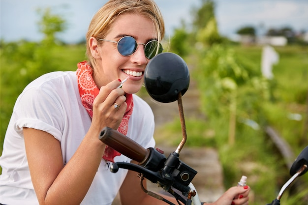 Modieuze blonde vrouwelijke fietser draagt tinten, schildert lippen met lippenstift, kijkt in de spiegel van de motor, geeft om een goed uiterlijk, houdt van vervoer en reizen in de open lucht. levensstijl en schoonheid
