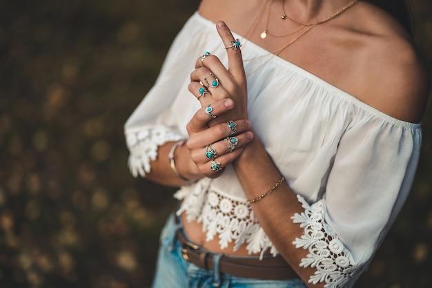Modieuze boho chic vrouw in een witte korte blouse met zilver turquoise sieraden