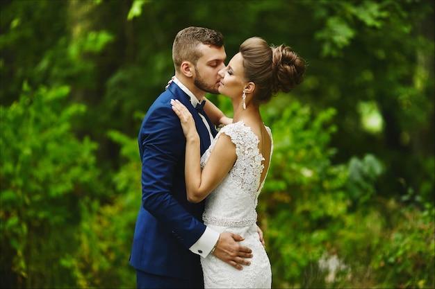 Modieuze bruidegom die prachtige bruid kust tijdens de huwelijksceremonie een liefdevol stel een meisje