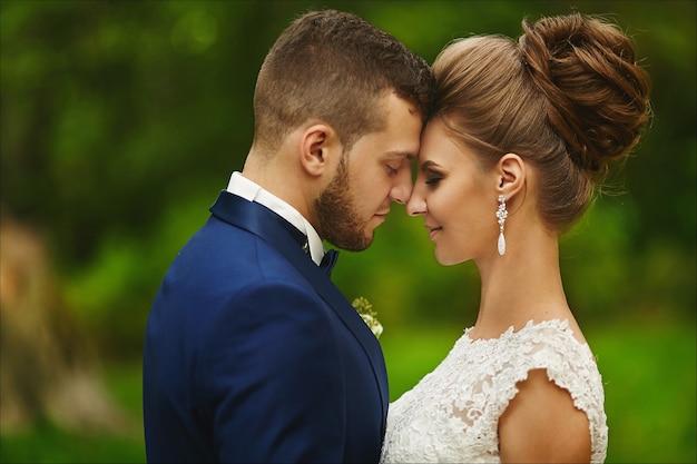 Modieuze bruidegom knuffelt een prachtige bruid tijdens de huwelijksceremonie een verliefd stel een vrouw