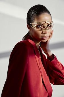 Modieuze brunette in rode blazer met ijzeren accessoire op gezicht close-up bijgesneden weergave