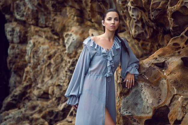 Modieuze brunette vrouw in een grijze jurk staat in de zomer op een kaasrots