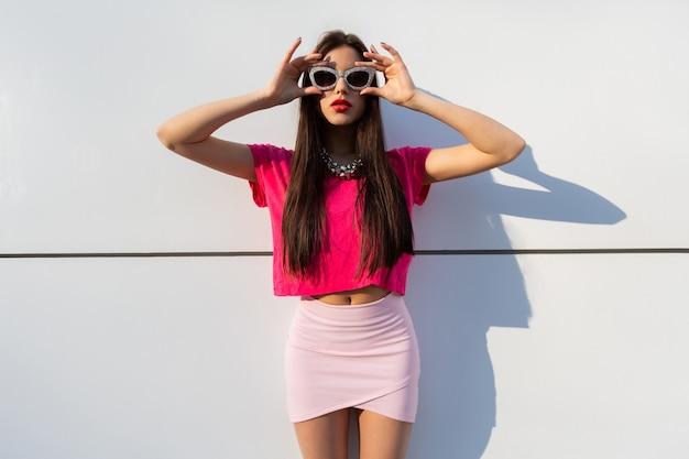 Modieuze brunette vrouw in zomerkleding en zonnebril poseren over witte stedelijke muur.