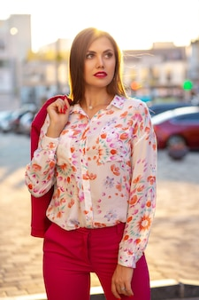 Modieuze brunette vrouw met blouse en roze jas die zich voordeed op de achtergrond van de avondstad