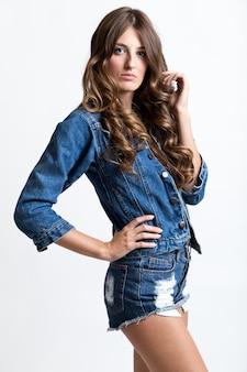 Modieuze brunette vrouw met lange slanke benen poseren in de studio.