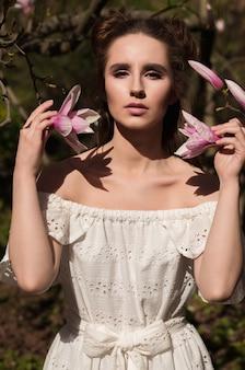 Modieuze brunette vrouw poseren in de buurt van de bloeiende magnoliaboom in witte kanten jurk