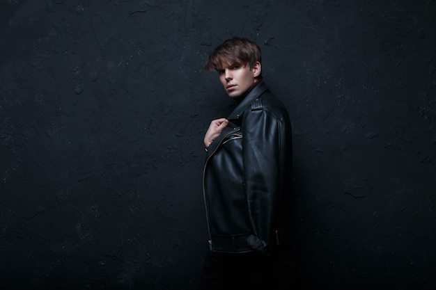 Modieuze coole jongeman met een kapsel in een zwart leren jasje in retro stijl met zwarte spijkerbroek staan en kijken in de camera in een donkere kamer in de buurt van de zwarte muur. leuke stijlvolle kerel.