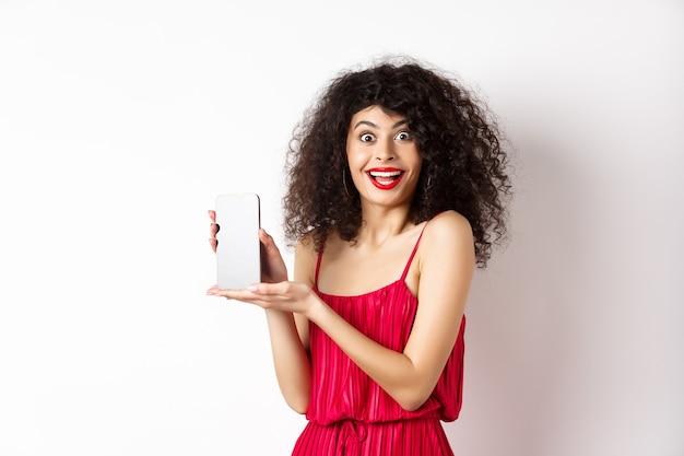 Modieuze dame in rode jurk en make-up, gsm-scherm tonen en glimlachen, smartphone-applicatie introduceren, staande op witte achtergrond.