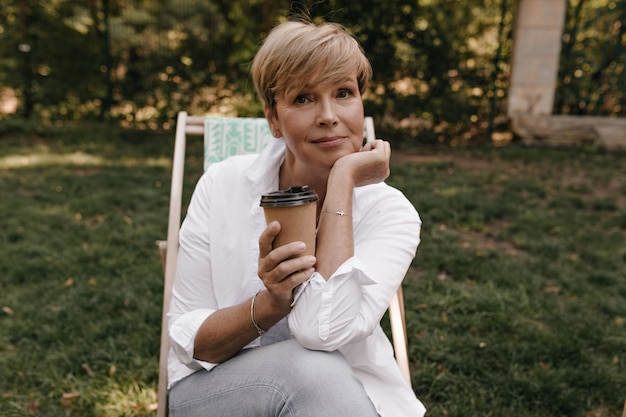 Modieuze dame met kort blond haar in licht shirt met lange mouwen en coole spijkerbroek op zoek naar camera en kopje thee buiten te houden.