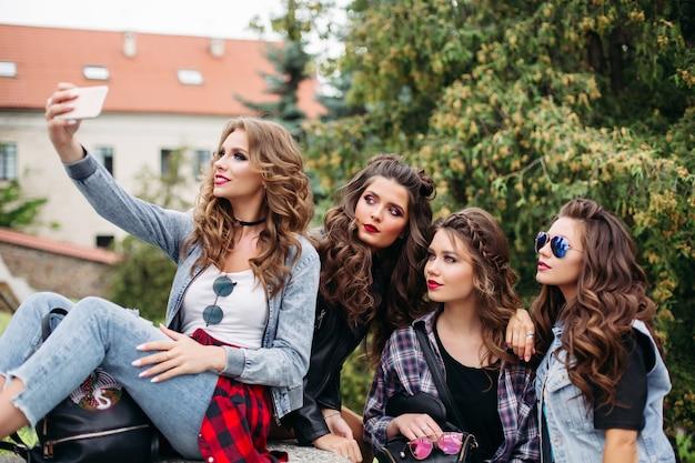 Modieuze dames met kapsel nemen selfie buitenshuis.