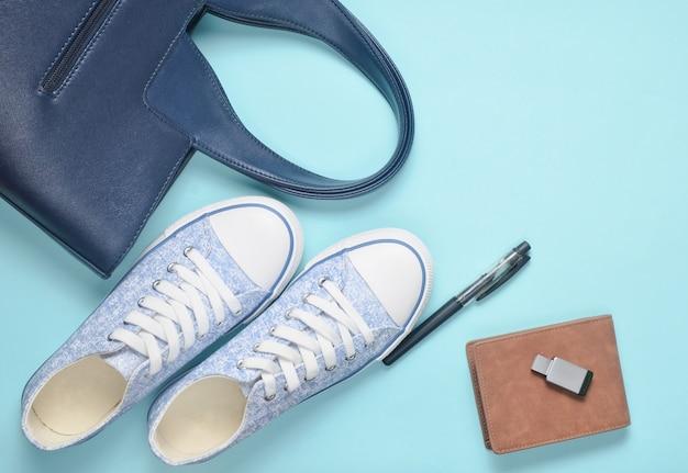 Modieuze damesaccessoires en apparaten op een grijze achtergrond: usb-stick, tas, portemonnee, sneakers, pen. bovenaanzicht plat liggen.