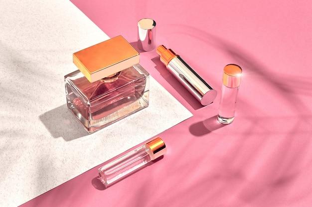 Modieuze damescosmetica en accessoires plat parfum roze en witte achtergrondschaduw van ...