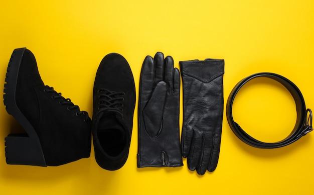 Modieuze damesschoenen en accessoires. laarzen, lederen riem en handschoenen op gele tafel. bovenaanzicht