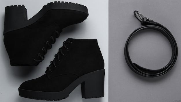 Modieuze damesschoenen en accessoires. laarzen, lederen riem op grijze tafel. bovenaanzicht