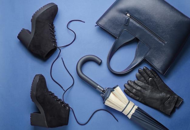Modieuze damesschoenen en accessoires op blauwe achtergrond. zwarte laarzen, tas, leren handschoenen, paraplu. bovenaanzicht