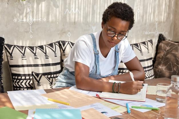 Modieuze donkere huid meisje studies grafiek, werkt met veel documenten, schrijft op in notitieblok