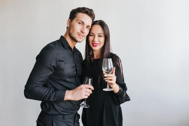 Modieuze donkerharige dame met een zachte glimlach die naar haar man leunt terwijl ze poseren op een feestje