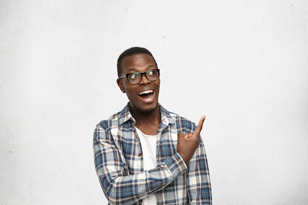 Modieuze emotionele jonge afro-amerikaanse man met trendy bril zijn wijsvinger wijzend op witte blinde muur
