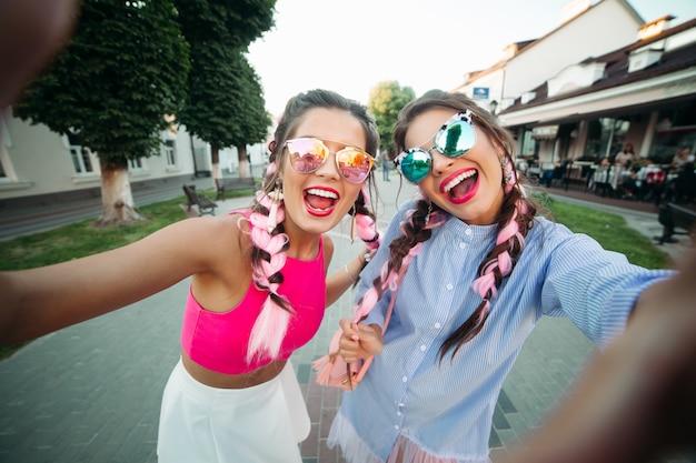 Modieuze en mooie beste vriendinnen in glazen, poseren doen zichzelf voor sociale netwerken