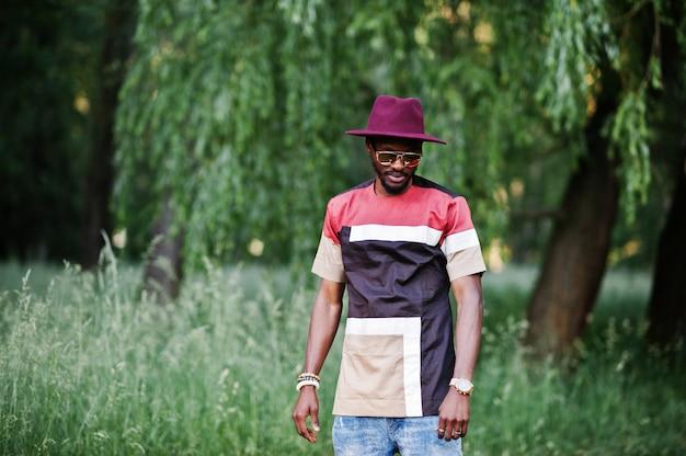 Modieuze en stijlvolle zwarte man met zonnebril en hoed