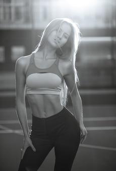 Modieuze fitnessvrouw met perfect lichaam die sportkleding draagt die zich voordeed op een tennisbaan in zonnestralen. zwart-witte kleur
