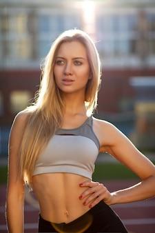 Modieuze fitte vrouw met getraind lichaam in sportkleding die zich voordeed op een tennisbaan in zonnestralen. vrouwelijk fitnessconcept