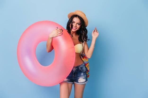Modieuze gelooide vrouw met roze zwemmende cirkel