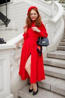 Modieuze gember vrouw in rode baret en elegante jurk poseren buiten.