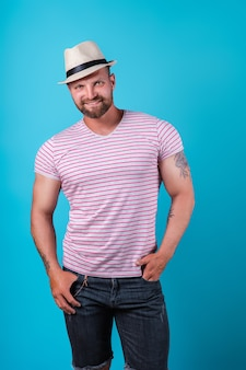 Modieuze gespierde bebaarde lachende man in stro hoed poseren in studio over blauwe achtergrond