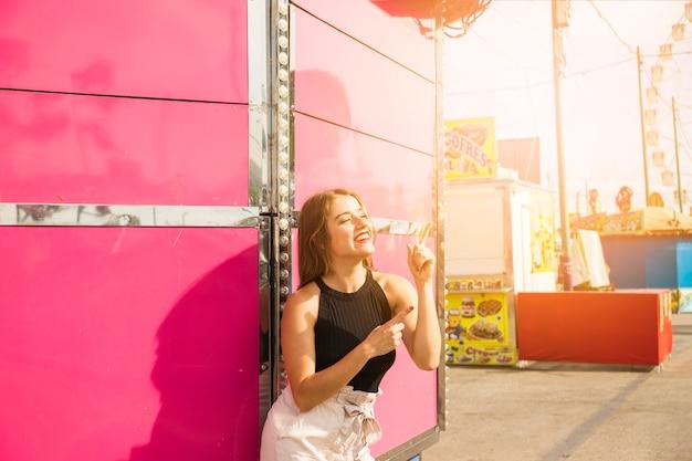 Modieuze glimlachende jonge vrouw bij pretpark