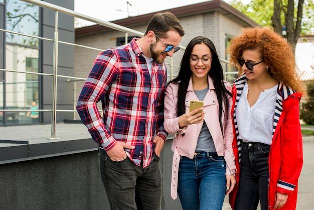 Modieuze glimlachende vrienden die mobiele telefoon bekijken