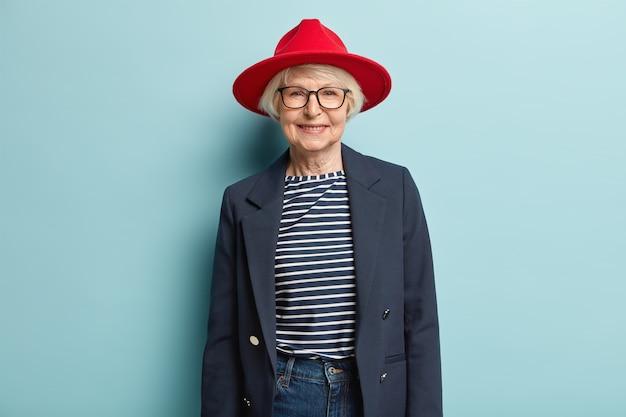 Modieuze grijze dame met gerimpeld gezicht, draagt rode stijlvolle hoed, jas en spijkerbroek, heeft een aangename glimlach