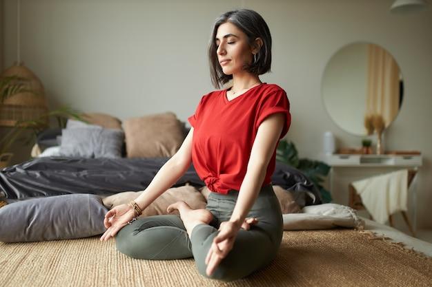 Modieuze grijze haren jonge vrouw yogi beoefenen van meditatie in haar slaapkamer, zittend in lotus houding, ogen sluiten en mudra gebaar maken